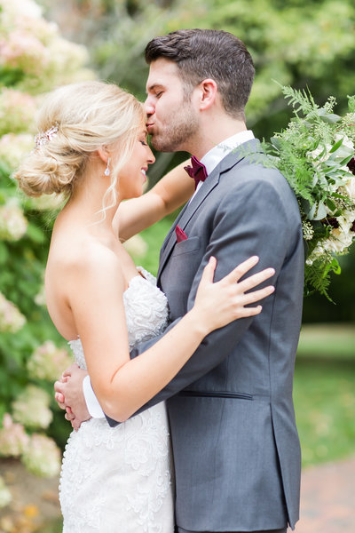 Groom kissing his brides forehead on their wedding day at Gervasi Vineyard photographed by akron ohio wedding photographer