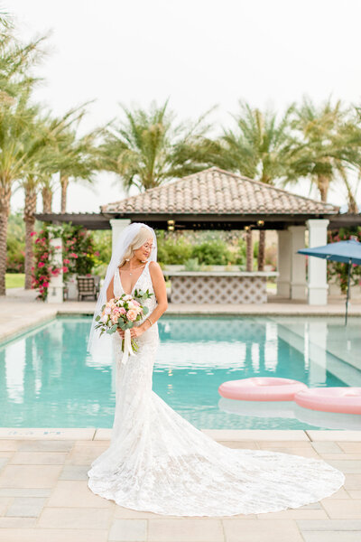 Bride posing with bouquet in front of pool in Palm Springs, California. Wedding photo taken by Cheers Babe Photo.