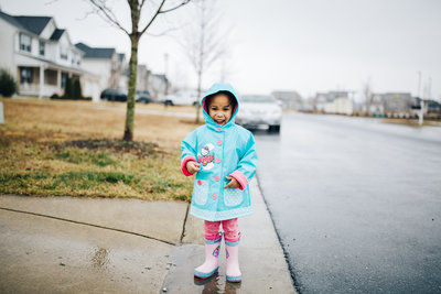 little girl in rain boots and a raincoat standing in a puddle outside in a driveway