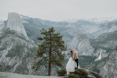 bride and groom kissing on top of a mountain
