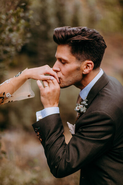 maroon bells elopement groom kissing brides hand