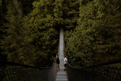 Couple standing on a bridge in a forest at their engagement session