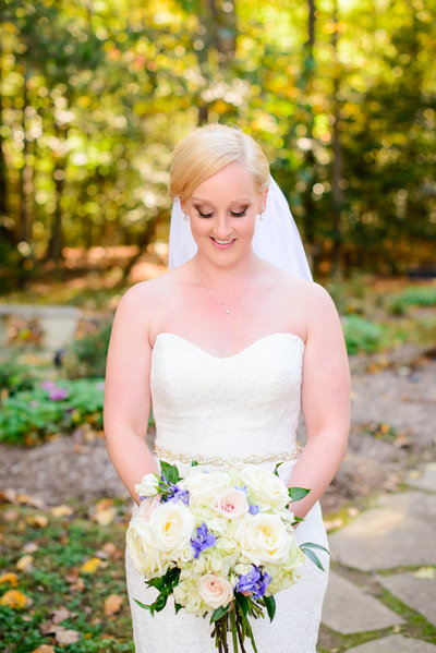 Bridal Portrait taken by DC Wedding Photographers BSP of a beautiful bride looking down at her wedding bouquette after her Eden Try  Wedding ceremony. The blue and white theme popped against the autumn colors of this romantic fall wedding in fredericksburg va.