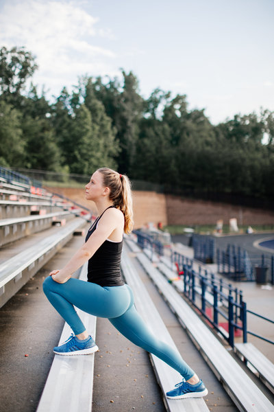 woman stretching on bleachers