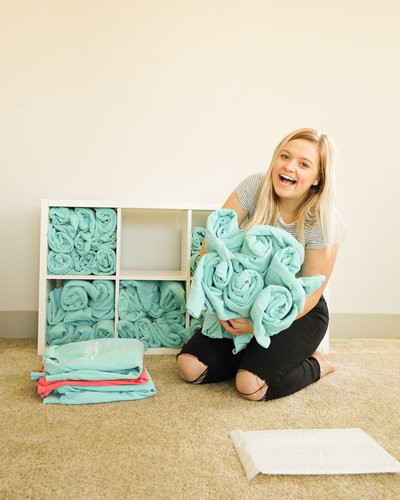 woman smiling and sitting on floors while holding teal towels