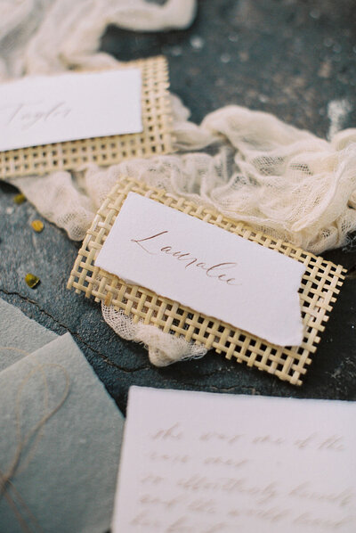 Wedding place card with berry colored calligraphy on cotton paper attached to a strip of open cane weave