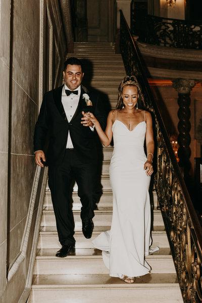 bride and groom walk down the stairs of the larz anderson house's grand ballroom in washington dc as they enter their wedding reception