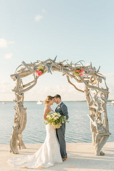 Bride and groom embrace under driftwood archway on the beach at their wedding in Key Largo