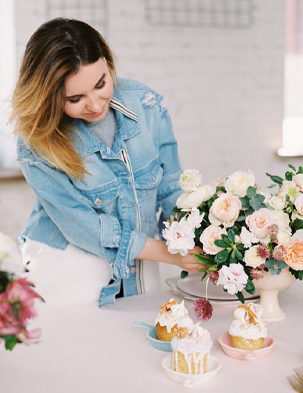 woman of color arranging lush flower arrangement with decorated cakes sitting nearby