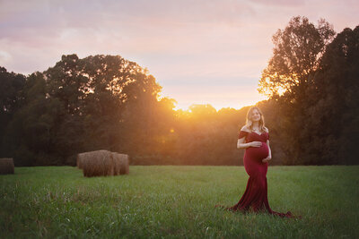 pregnant mom in field sunset with hay bales