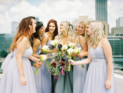 Bride and Bridesmaids wearing purple tulle gowns standing together and laughing with their bouquets on an Atlanta rooftop with the city skyline behind