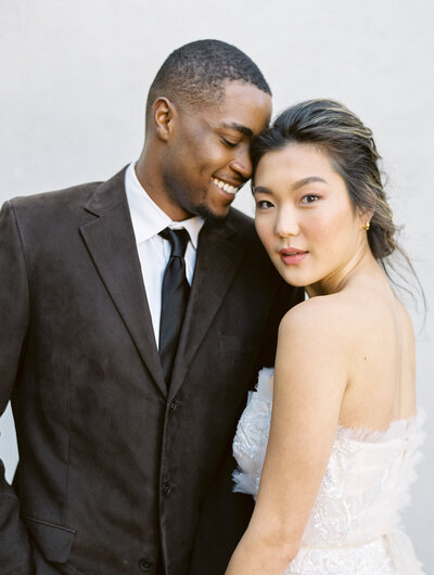 black groom in a brown suit turning towards his asian bride who is smiling for the camera