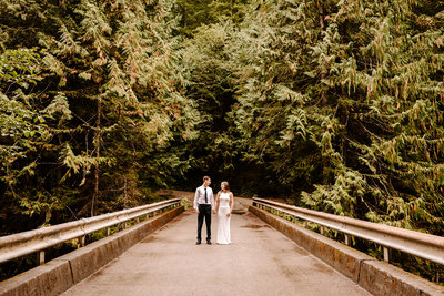 newly weds standing on a bridge for their first dance