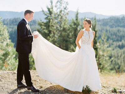 groom holding bride's dress as she looks back at him