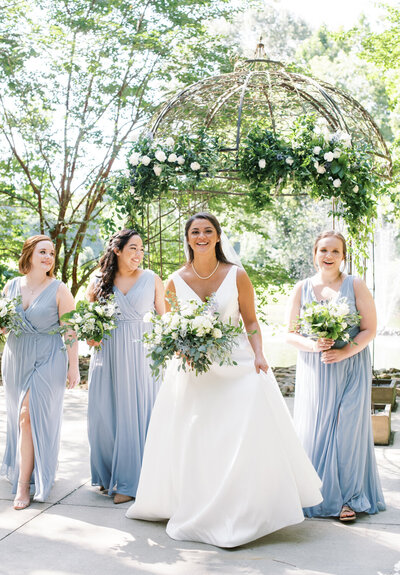 Bride and bridesmaids in dusty blue walking in front of fountain
