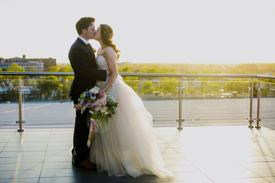 bride and groom rooftop kiss in charleston