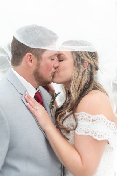 Bride and groom under veil at Raccoon Creek