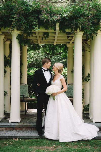 Bride in Amsale Coco Wedding Dress with White Peony Bouquet with Groom in Black Tuxedo  in Charleston Garden