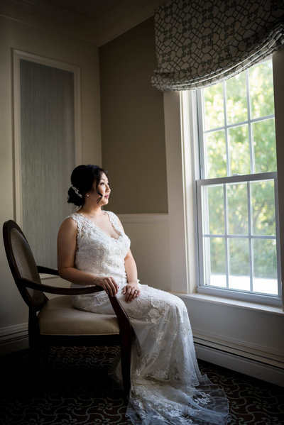 bride looking out the window Saphire Estate in Sharon MA