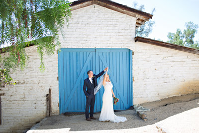 Bride and Groom dancing in front of blue barn door at Leo Carrillo Ranch
