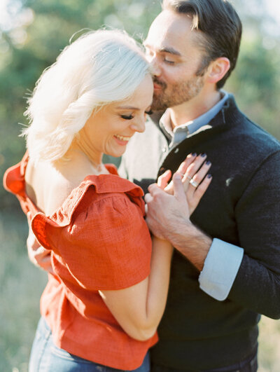 Man kisses woman's forehead while she closes her eyes and smiles during engagement photography session