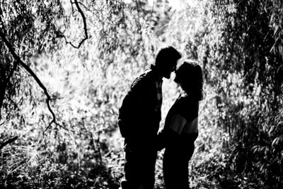 Engaged couple touch noses  among trees during engagement photos at Frontier Park in Erie, PA
