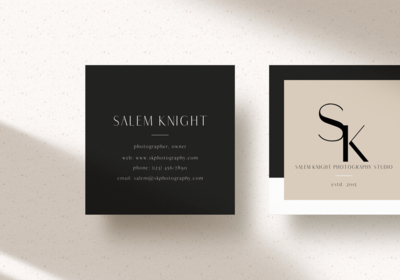A mockup of the Salem Knight business cards; the back of the card, on the left side of the picture,  is black with white text while the front of the card, seen on the right, is a half black, half white border with cream in the middle and the logo on front