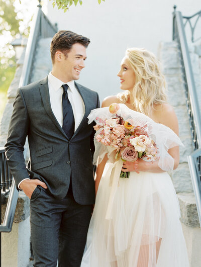 Stylish bride and groom descend stairs while smiling at one another