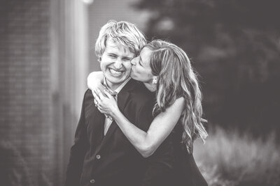 A cute photo of a bride kissing her groom while he is laughing during an outdoor engagement session.