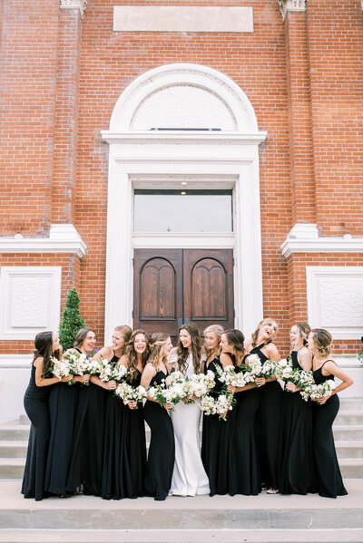 bride stands in the center of her bridesmaids all wearing black dresses holding their white and green bridesmaid bouquets on the steps of the monastery event center in cincinnati ohio bridal bouquet made by cincinnati wedding florist roots floral design