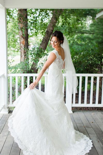 Bride adjusting her wedding dress on a Minnesota porch