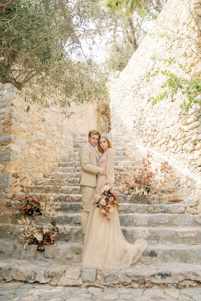 Bride and groom embrace on stone staircase in Greece