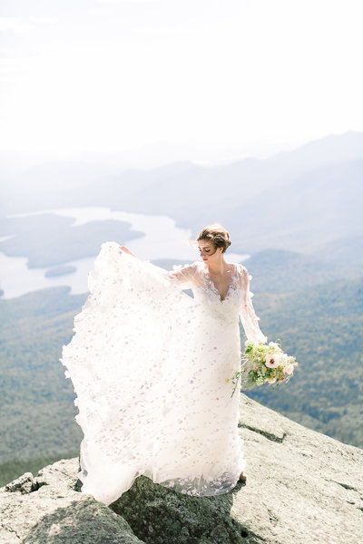 A bride on a  Maine mountaintop with sun shining through her gown