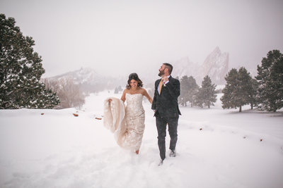 Bride and groom running through the snow at winter wedding in Colorado