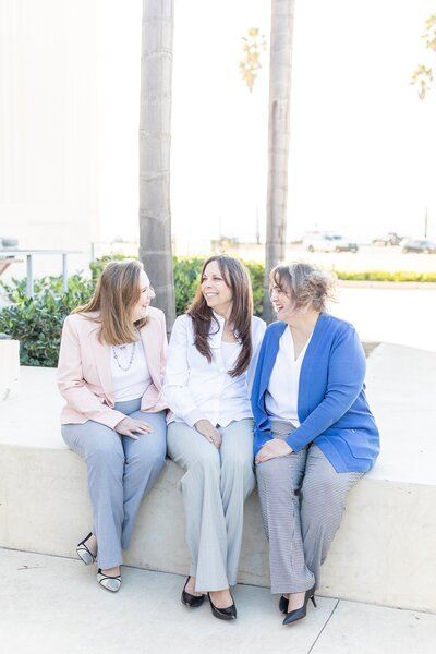 Circe Solutions owners, Connie, Tracy Narvet, and Colette Martin, sitting in front of San Diego County Courthouse.