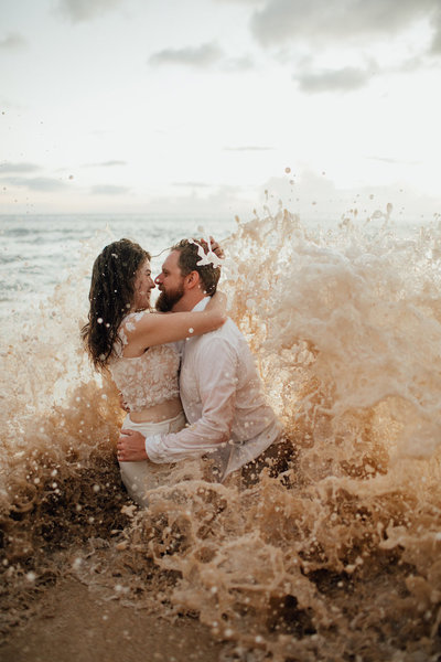 couple standing in crashing waves
