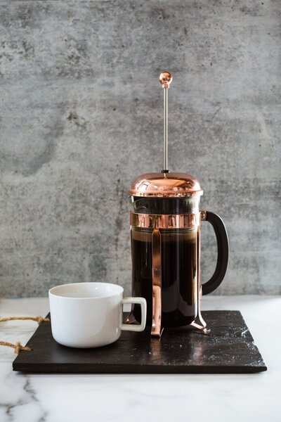 morning-scene-on-a-white-marble-surface-with-a-grey-cement-background-a-copper-french-press-pot-full_t20_3QrZL3