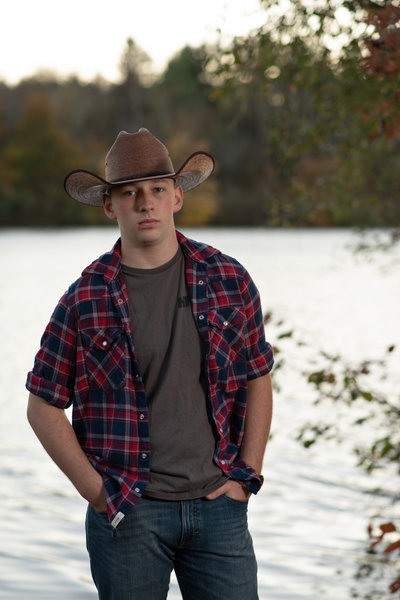 Senior guy in western hat and flannel in front of lake