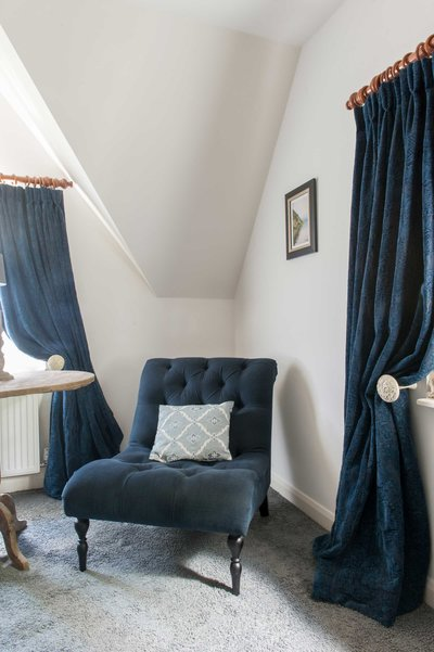 Chair by sofa.com and curtains made from Arte di Vita fabric in one of the bedrooms at Bank Cottage in the Cotswolds, England. Realised by Arte di Vita Interiors.