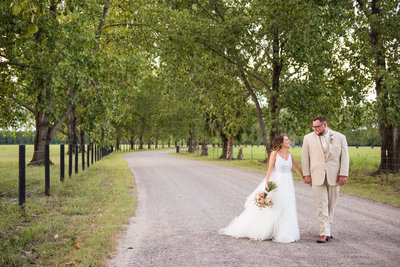 Couple walking in between a row of pecan trees