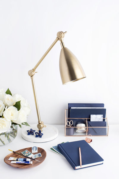 white desk with brushed brass lamp and navy blue notebook, stamps, white roses, and a desk organizer