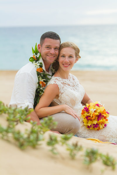 Bride and groom sitting in the white sand with tropical lei and bouquet.