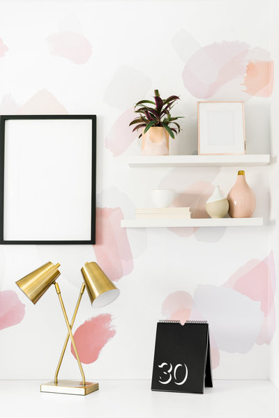 Pink and white wallpapered office with desk accessories