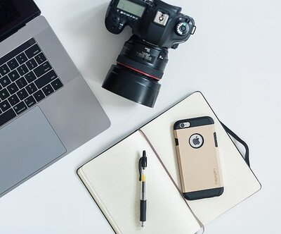 laptop camera phone notebook pen flatlay
