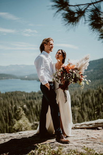 Couple smiling on a lake overlook after ceremony in Lake Tahoe, CA