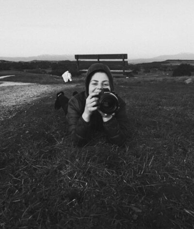 woman smiling taking photos laying on the ground