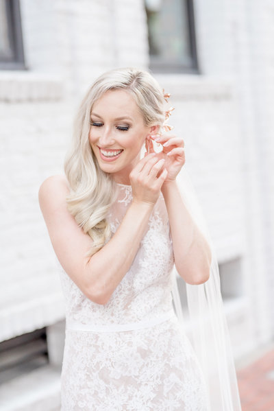 Beautiful bride adjusts her jewelry on her wedding day