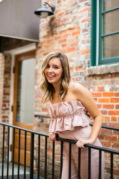 Teen girl poses in front of brick wall in urban area during senior portrait session