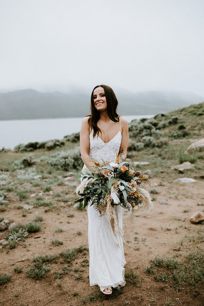 A bride smiles with her bouquet in front of a lake.