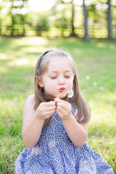 Jennifer Laura Photography young girl making a wish by blowing a dandelion
